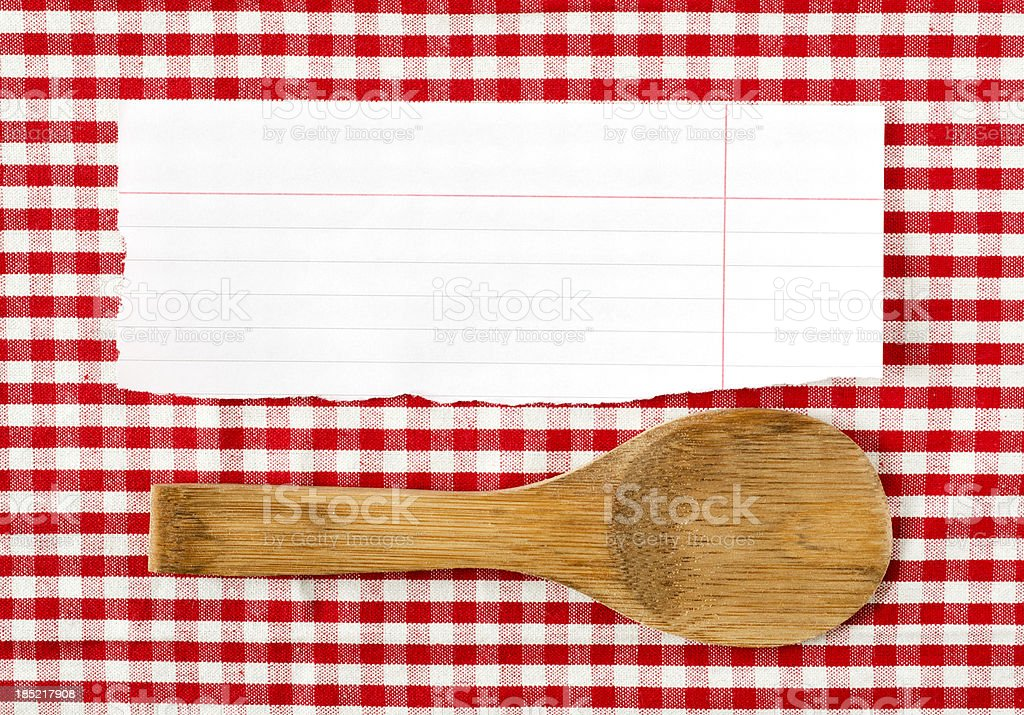 Wooden spoon and paper on red tableclot royalty-free stock photo