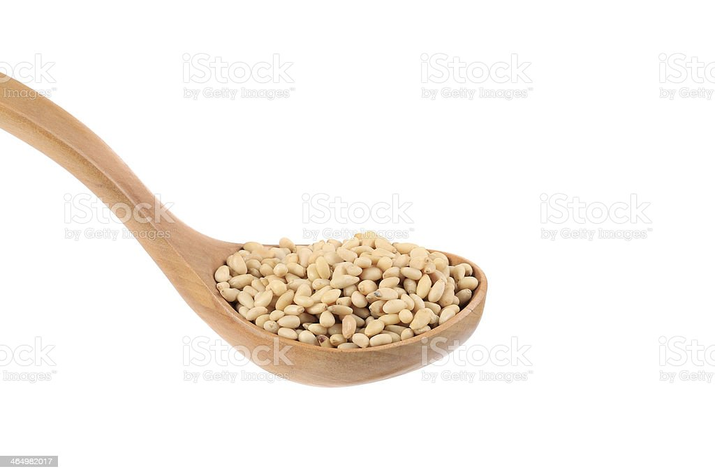 Wooden spoon full with pine nuts. stock photo
