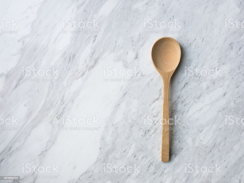 Wooden Spoon on white marble. stock photo