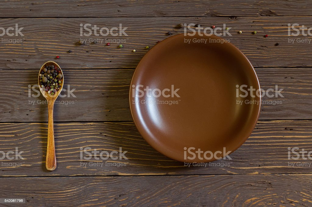 Wooden Spoon With Colored Pepper Lies On The Boards. Plate stock photo