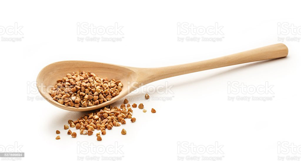 Wooden spoon with dry buckwheat stock photo
