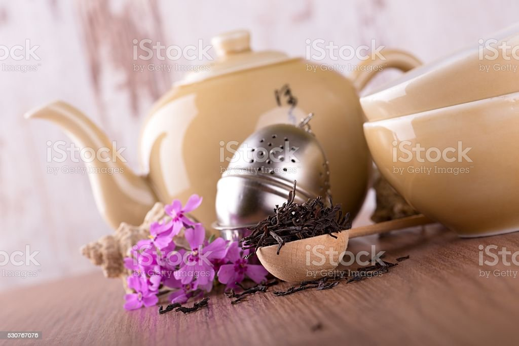 Wooden spoon with dry tea and tea set stock photo
