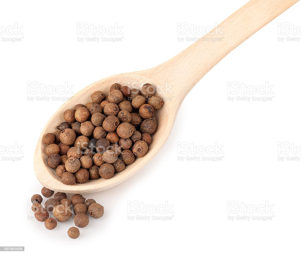 wooden spoon with pimento peppercorns isolated on white backgrou stock photo