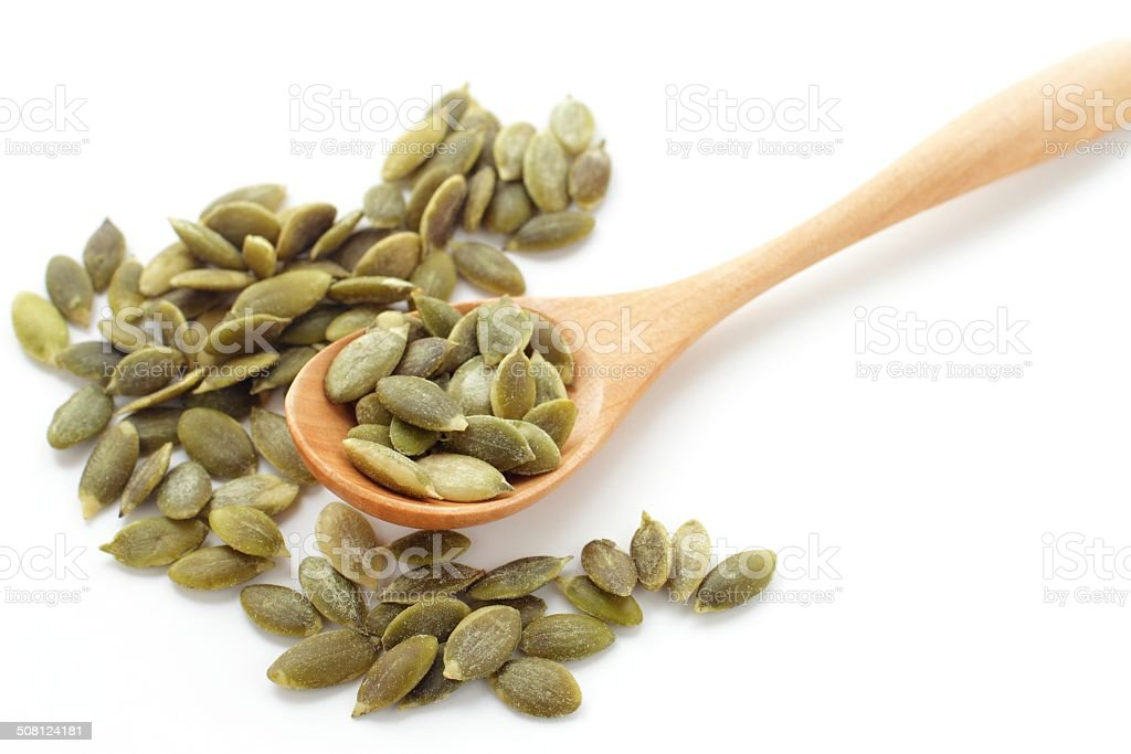 Wooden spoon with pumpkin seeds. stock photo