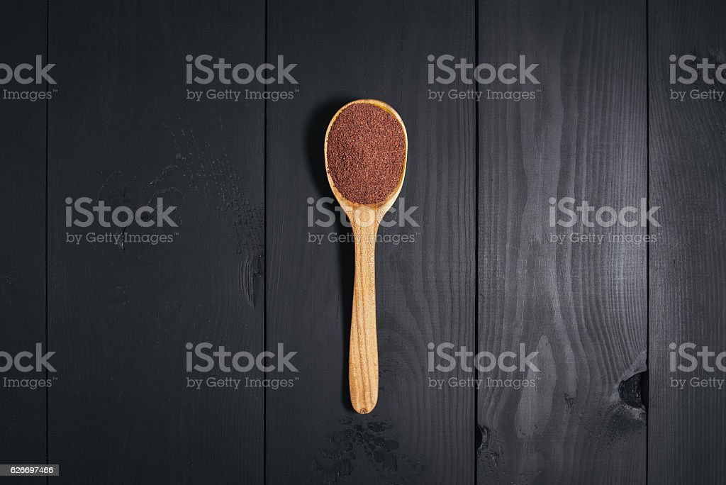 Wooden spoon with spices on a black background. stock photo