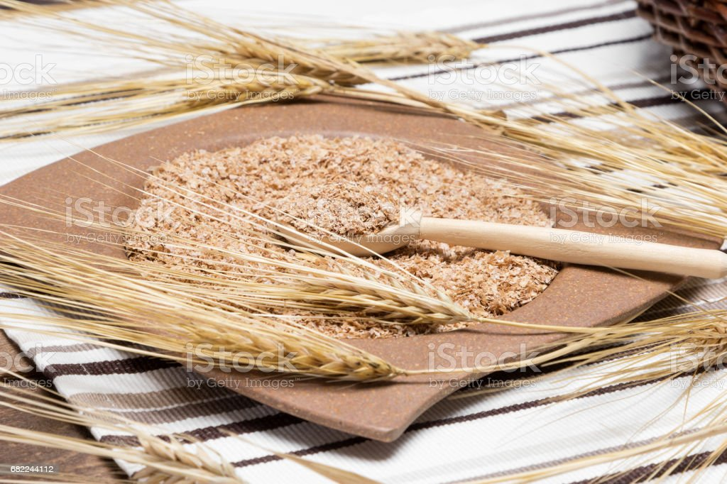 Wooden spoon with wheat bran and wheat ears stock photo
