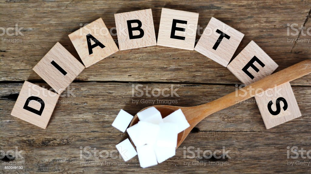 Wooden spoon with white sugar cubes indicating high risk of diabetes stock photo