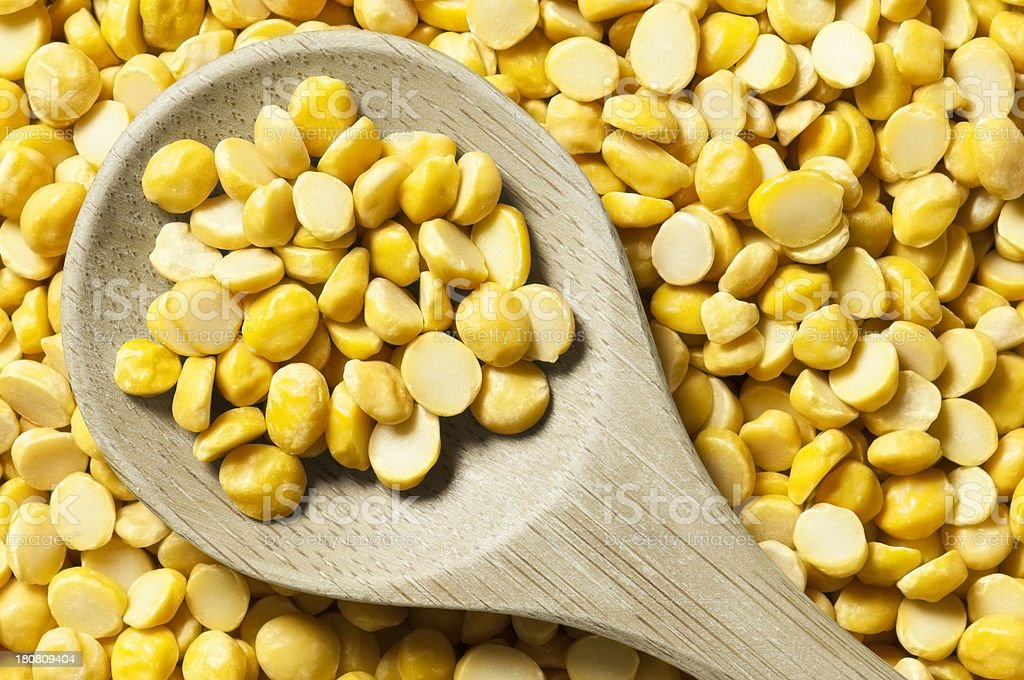 Wooden spoonful of dried split peas lying on chana dal stock photo