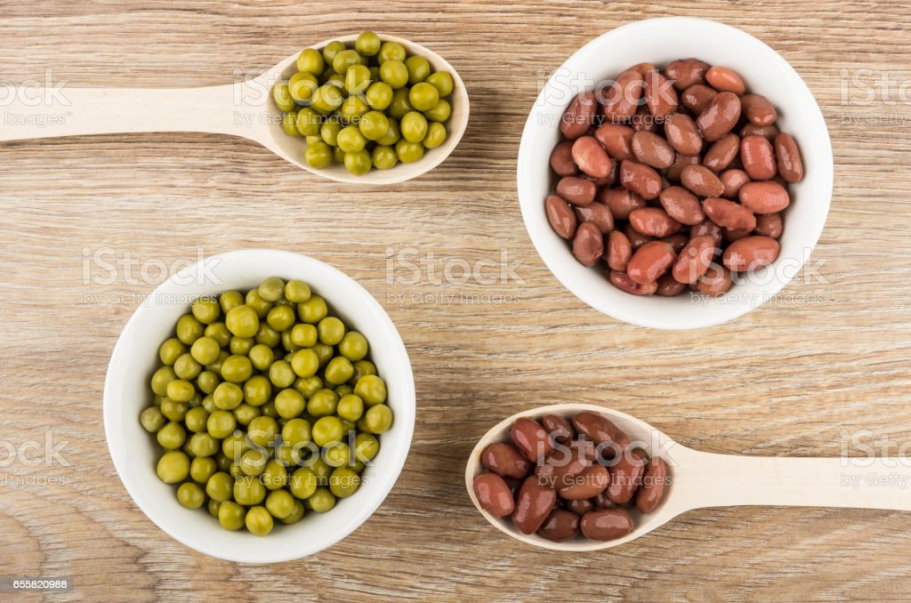 Wooden spoons, bowls with red baked beans and green peas stock photo