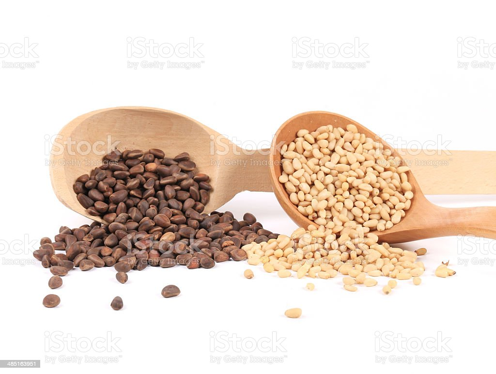 Wooden spoons full with pine nuts. stock photo