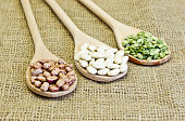Wooden spoons hold beans and peas