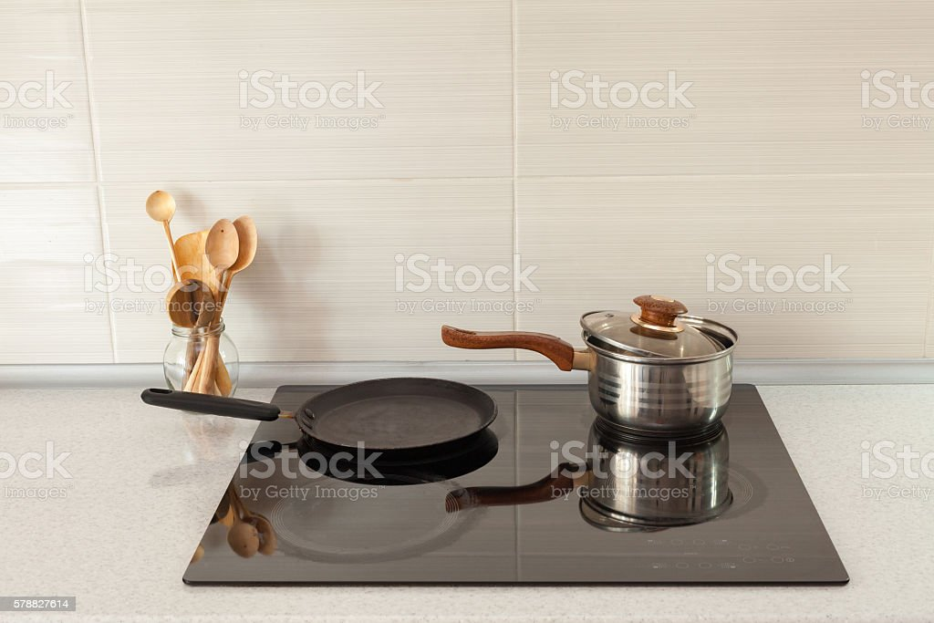 Wooden spoons in modern kitchen with induction stove stock photo
