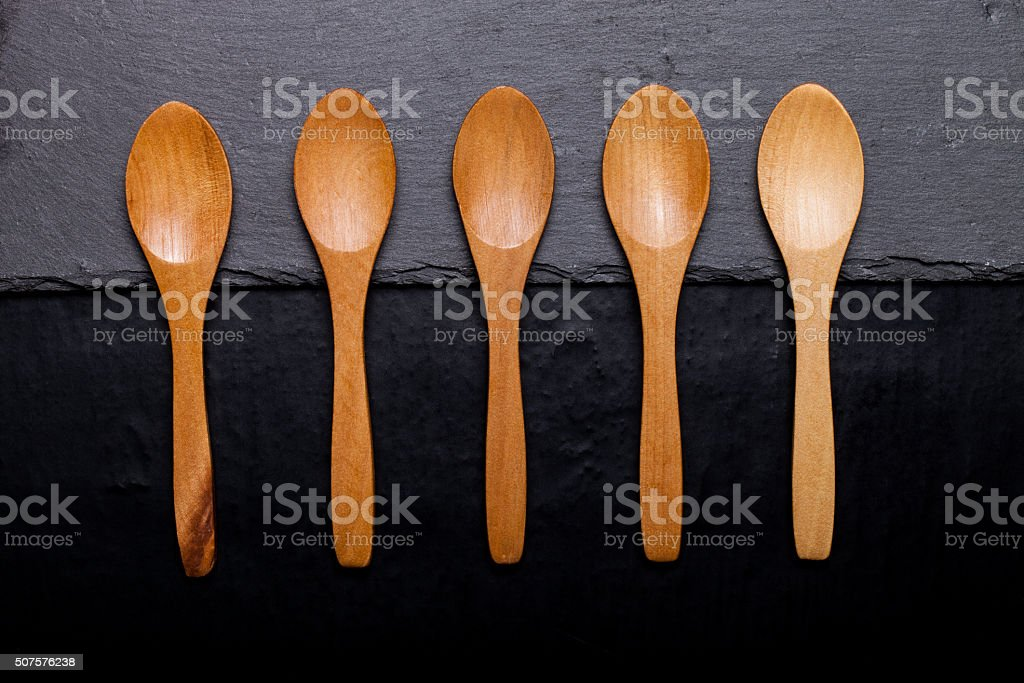 Wooden spoons on a plate of slate stock photo