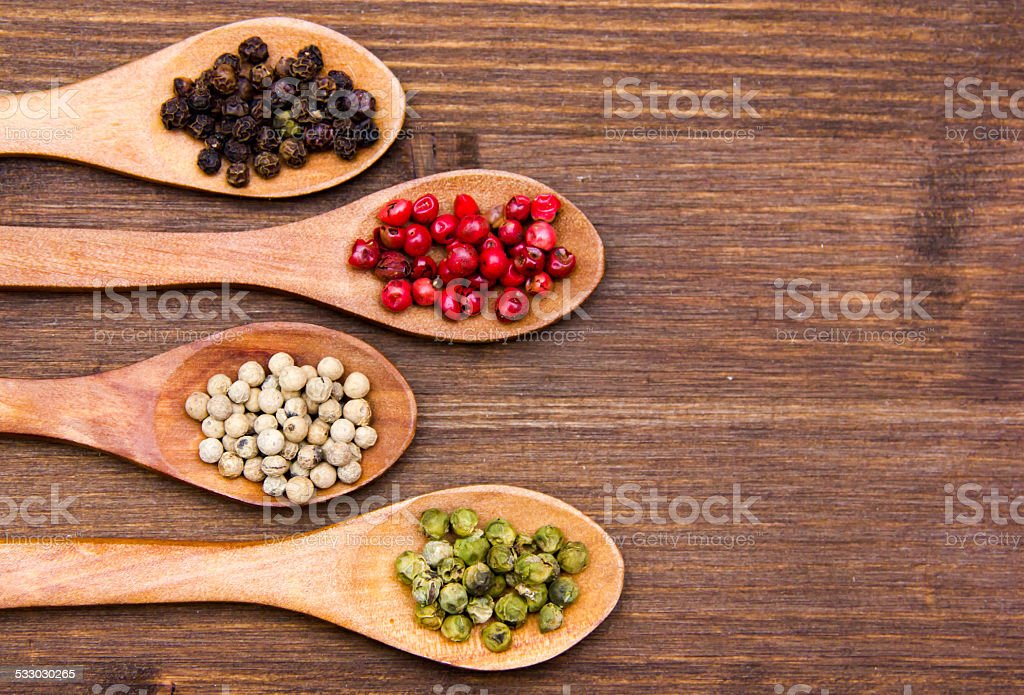 Wooden spoons with peppers mixed one hand on wood stock photo