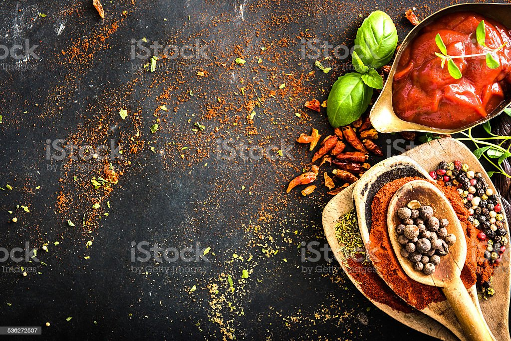 Wooden spoons with spices and tomato sauce stock photo