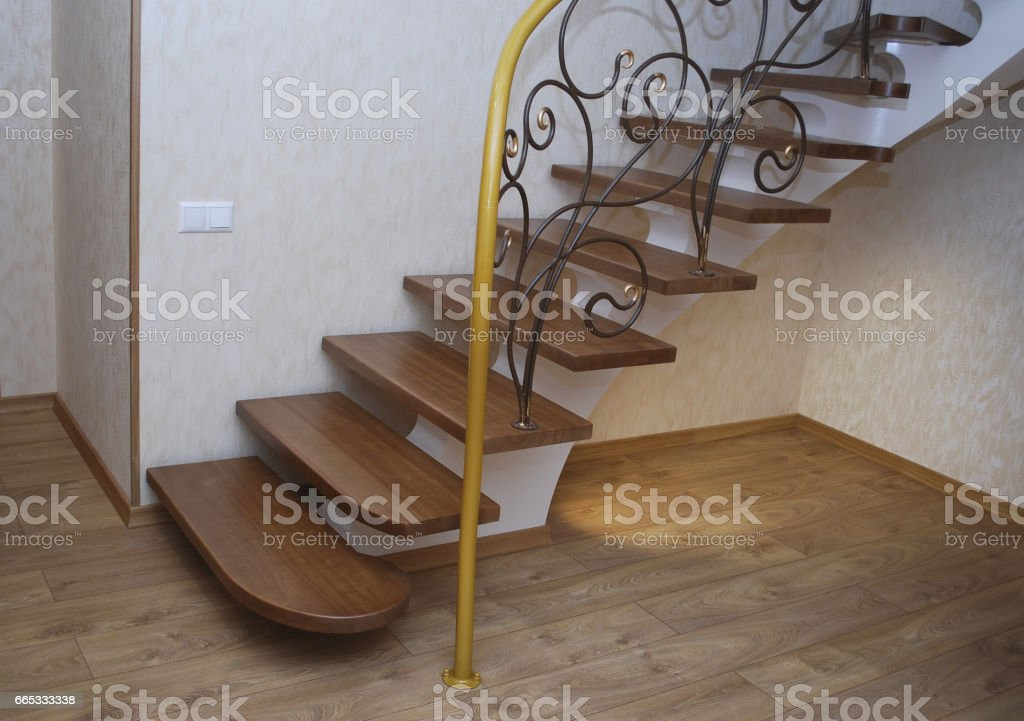 Wooden stairs and metal tracery forged railing. stock photo