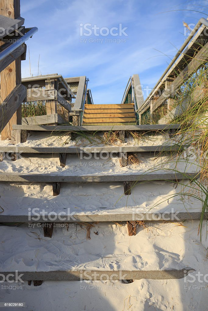 Wooden stairway leads to the wide sandy beach royalty-free stock photo