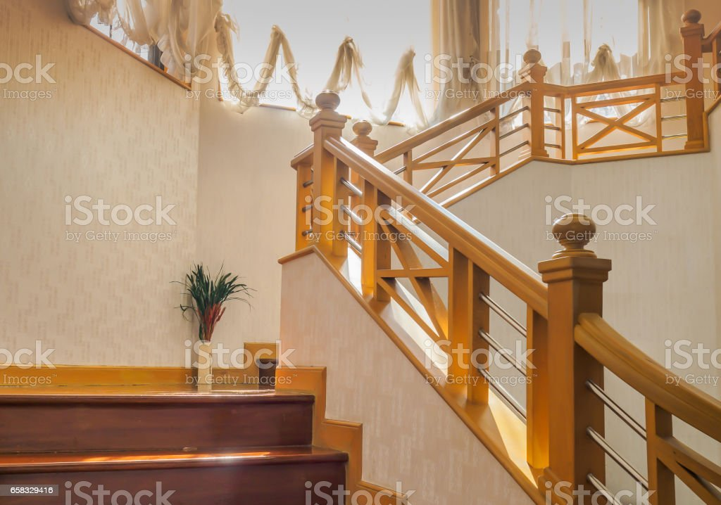 Wooden stairway with handrail and stainless banister, white wall, modern home interior. stock photo