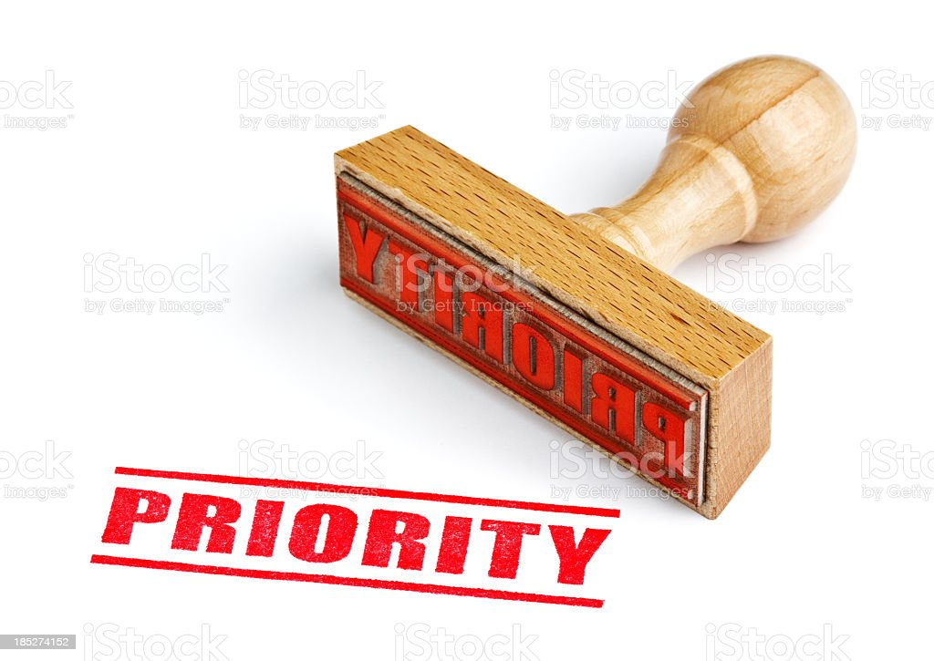 A wooden stamp about priority in a white background stock photo
