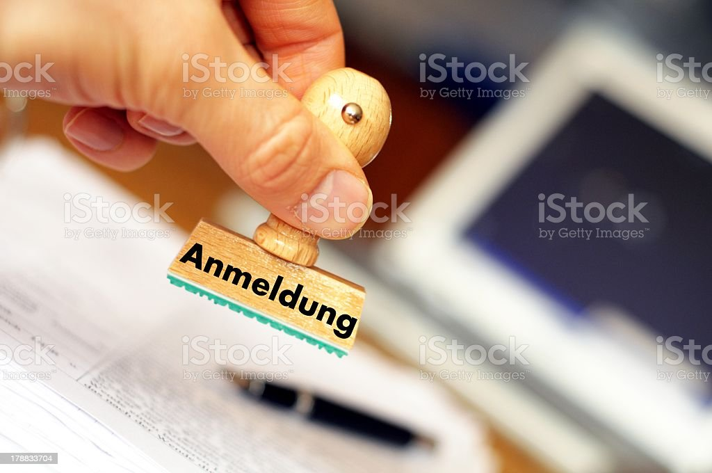 A wooden stamp with the word Anmeldung on it stock photo