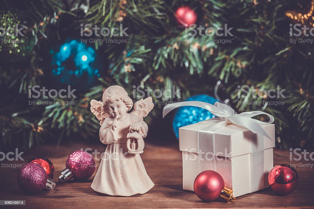 Wooden statue at christmas background with gift box, toned stock photo