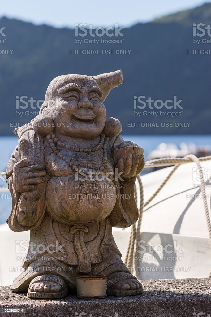 Wooden statue of Ebisu at Lake Ashi shore. stock photo