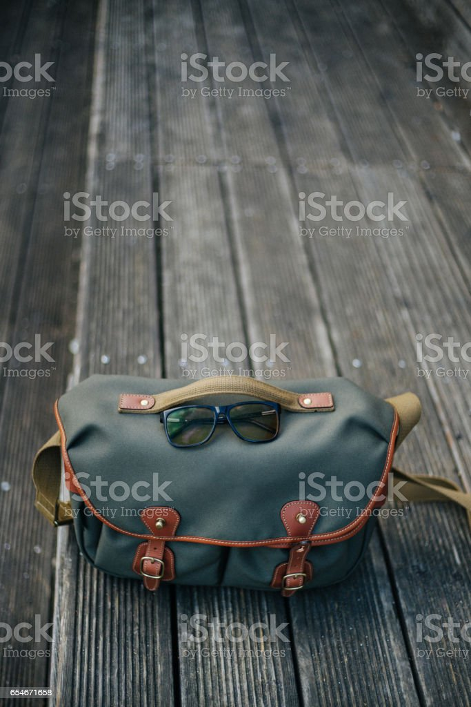 Wooden surface and the retro bag stock photo
