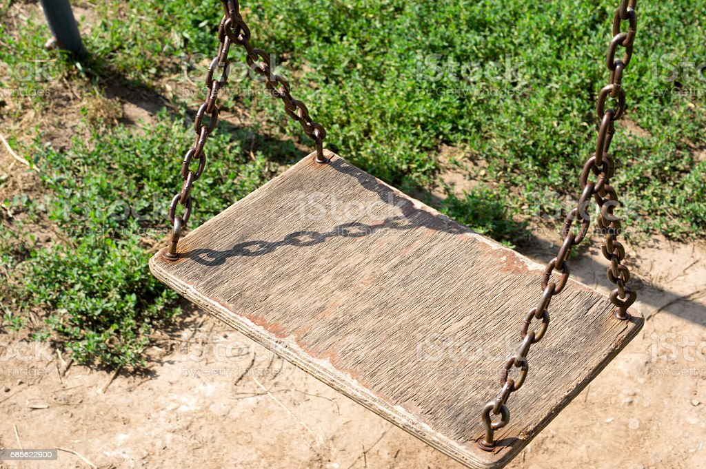 Wooden swing hanging from chains in the yard stock photo