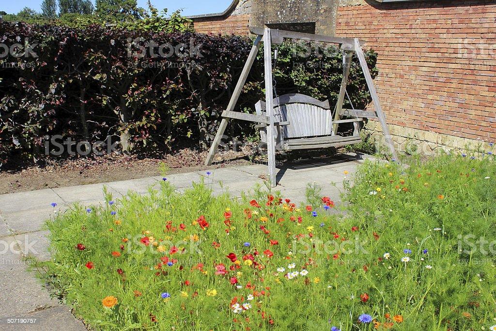 Wooden swing seat in wildflower garden, copper beech hedge image stock photo