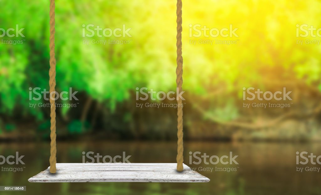 wooden swing with nature blurred background stock photo