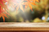 Wooden table and blur maple leaf background.