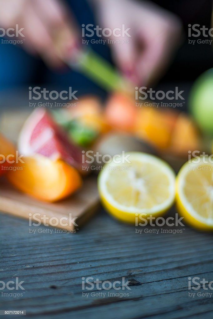 Wooden table and blurred fruit in background stock photo
