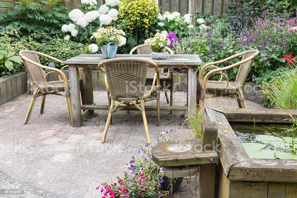 Wooden table and chairs in a ornamental garden stock photo
