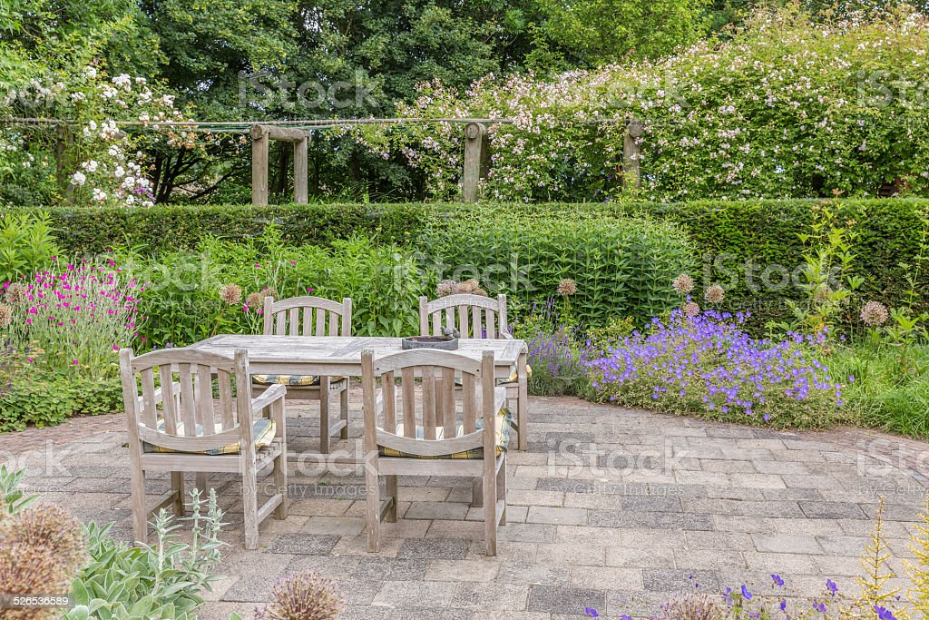 Wooden table and chairs in an ornamental garden stock photo