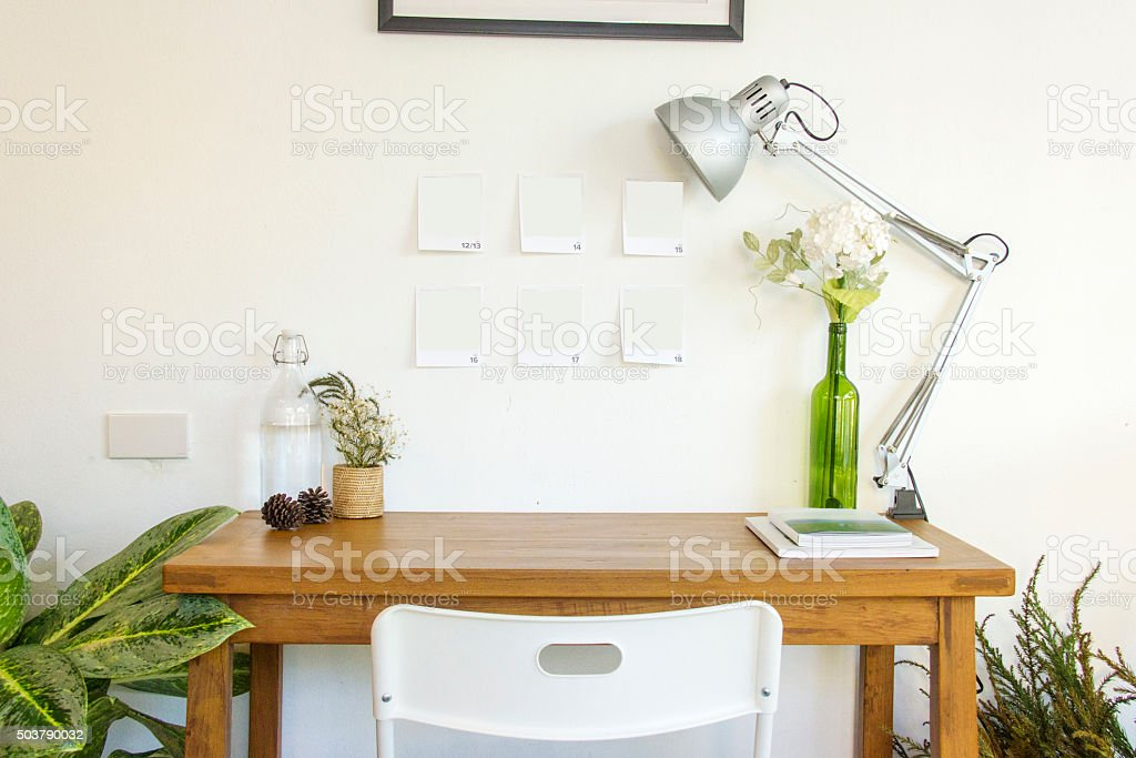 Wooden table and decorative elements in white room stock photo