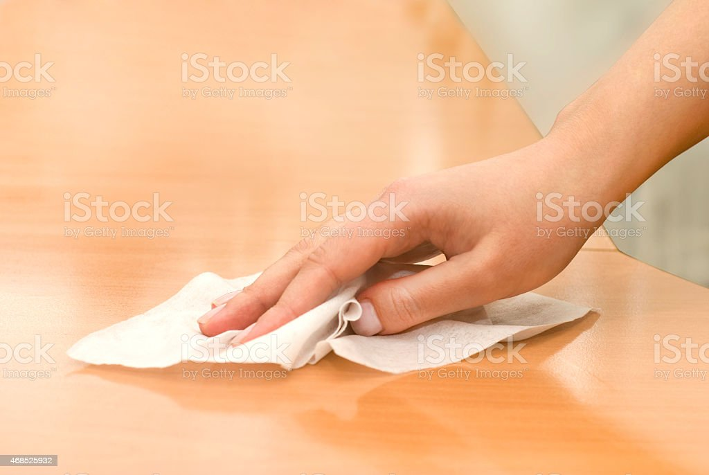 A wooden table being wiped off with a wet wipe  stock photo