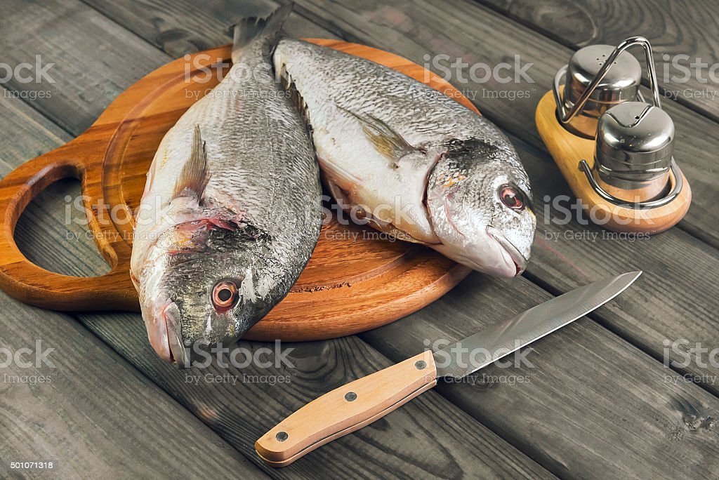 wooden table cutting board with fresh raw dorado fish stock photo