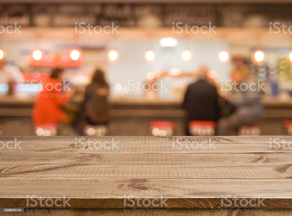 Wooden table in front of abstract blurred bar counter background stock photo