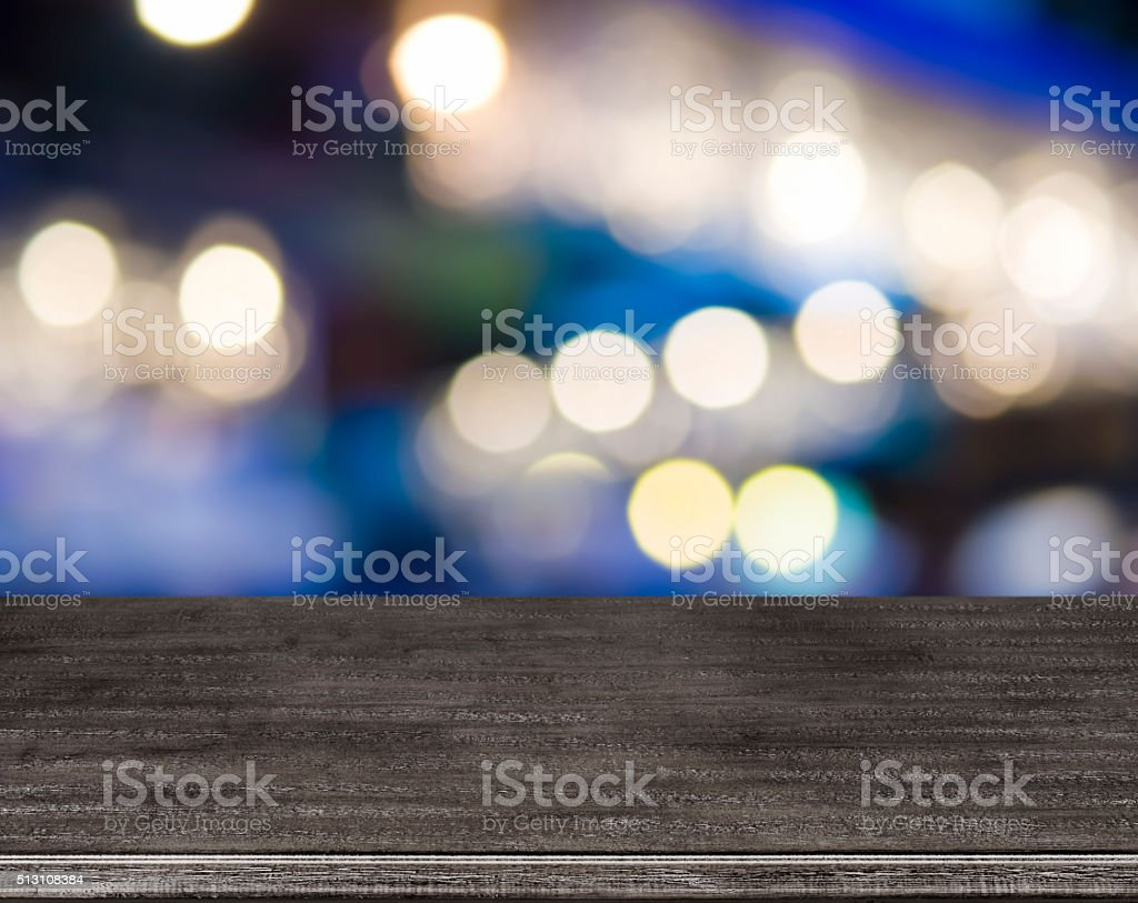 Wooden table in front of abstract blurred street lights background stock photo