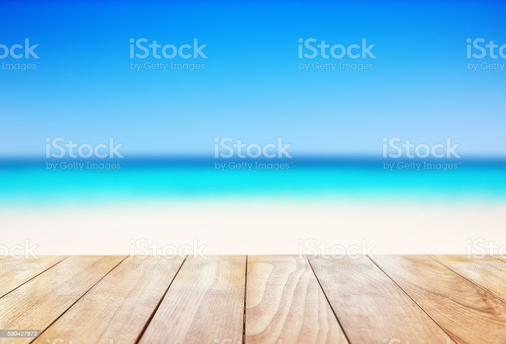 Wooden table on blue sea and white sand beach stock photo