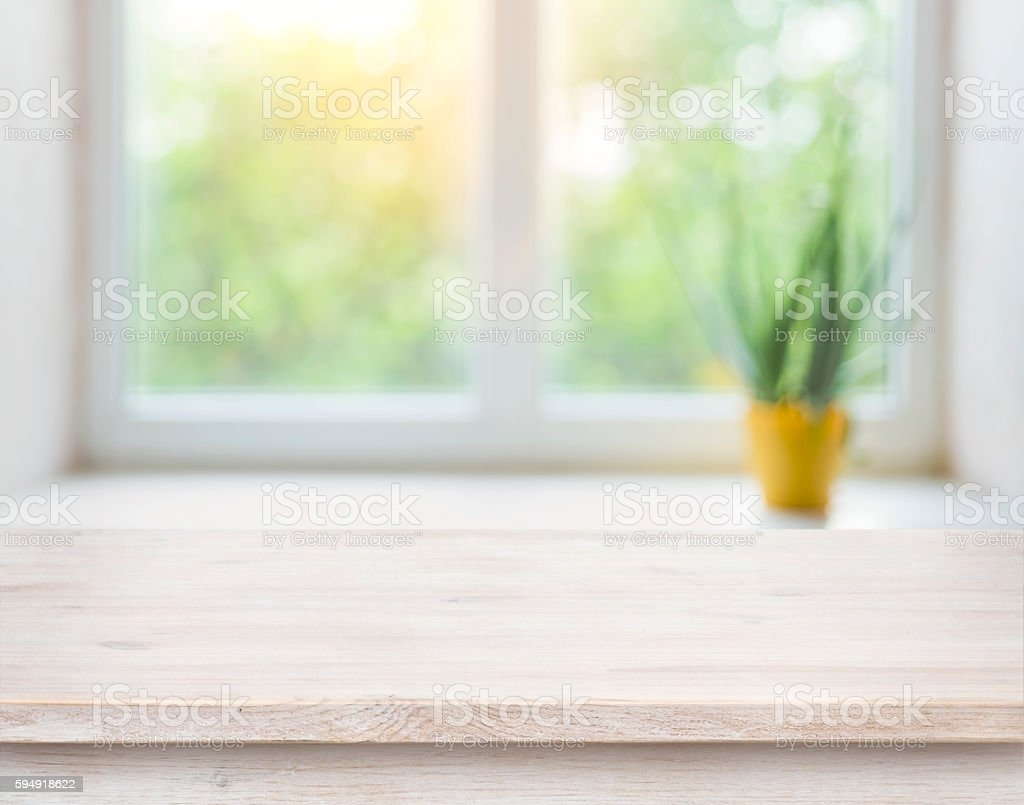 Wooden table on blurred autumn window with plant pot background stock photo