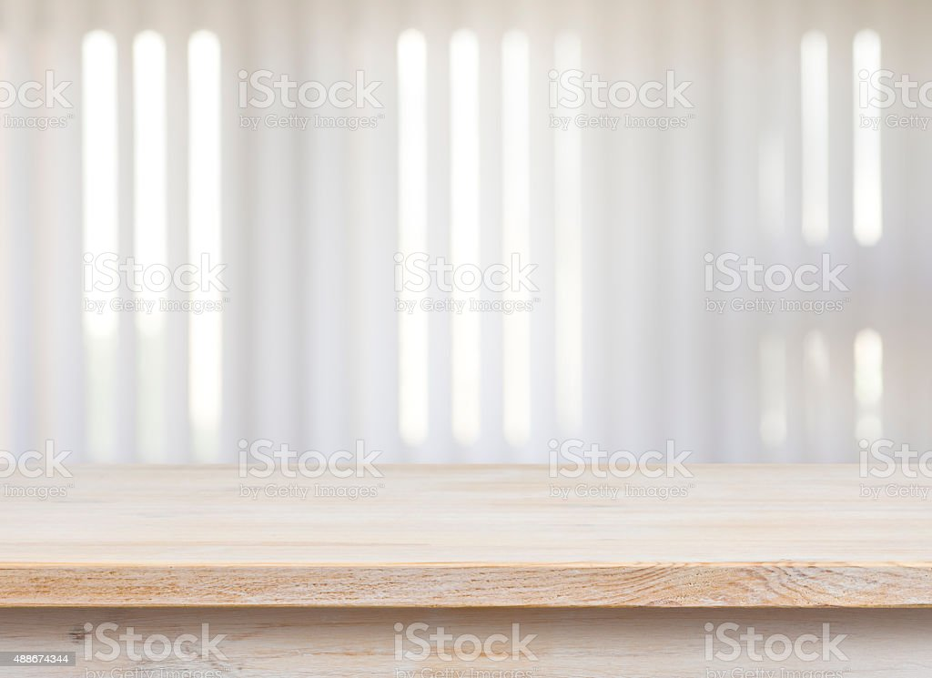 Wooden table on defocuced window with jalousie background stock photo