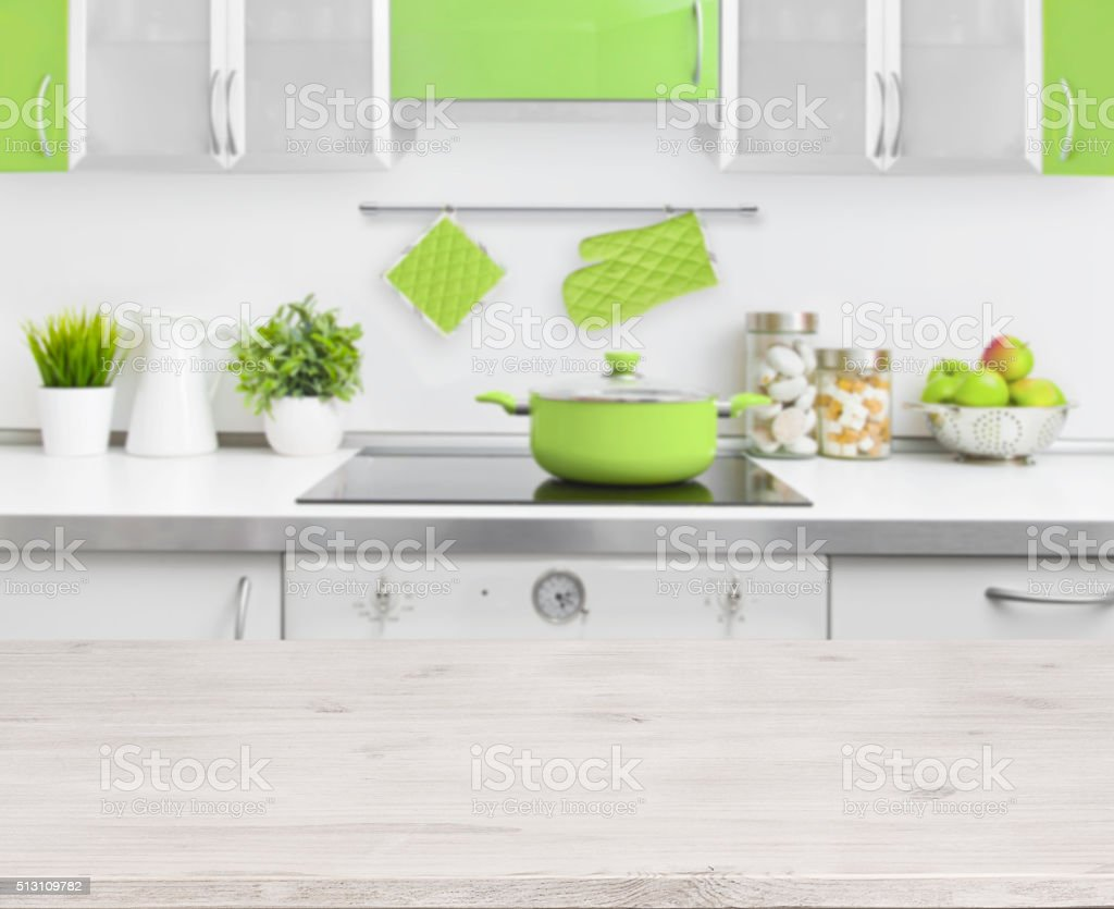 Wooden table on green modern kitchen bench interior background stock photo