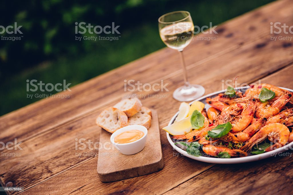 Wooden table outdoors with barbecued prawns and white wine stock photo