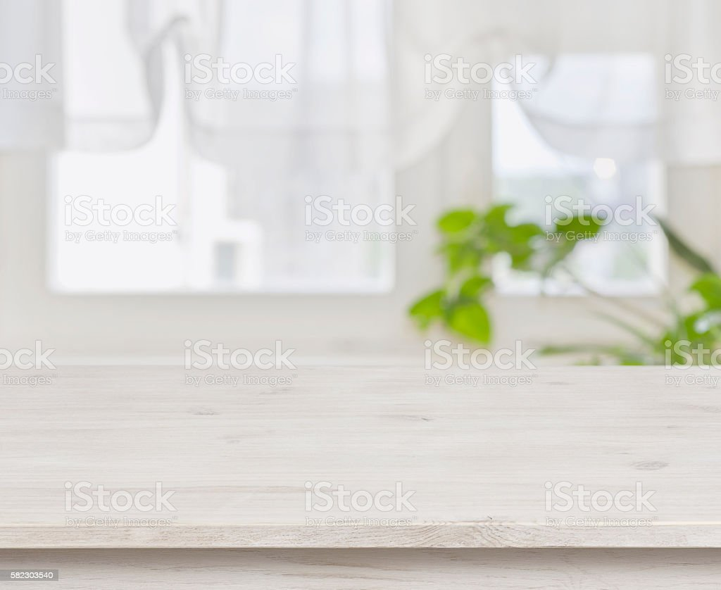 Wooden table over defocused green leaves and curtained window background stock photo