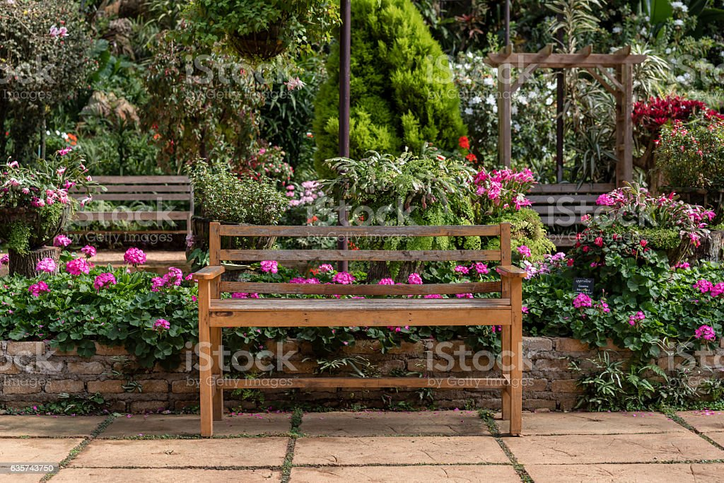 wooden table set in a flower garden stock photo