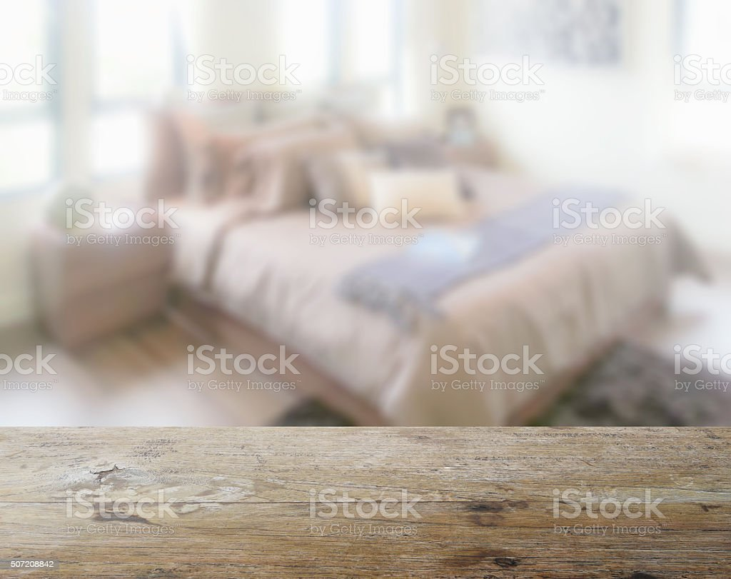 wooden table top with blur of bedroom interior as background stock photo