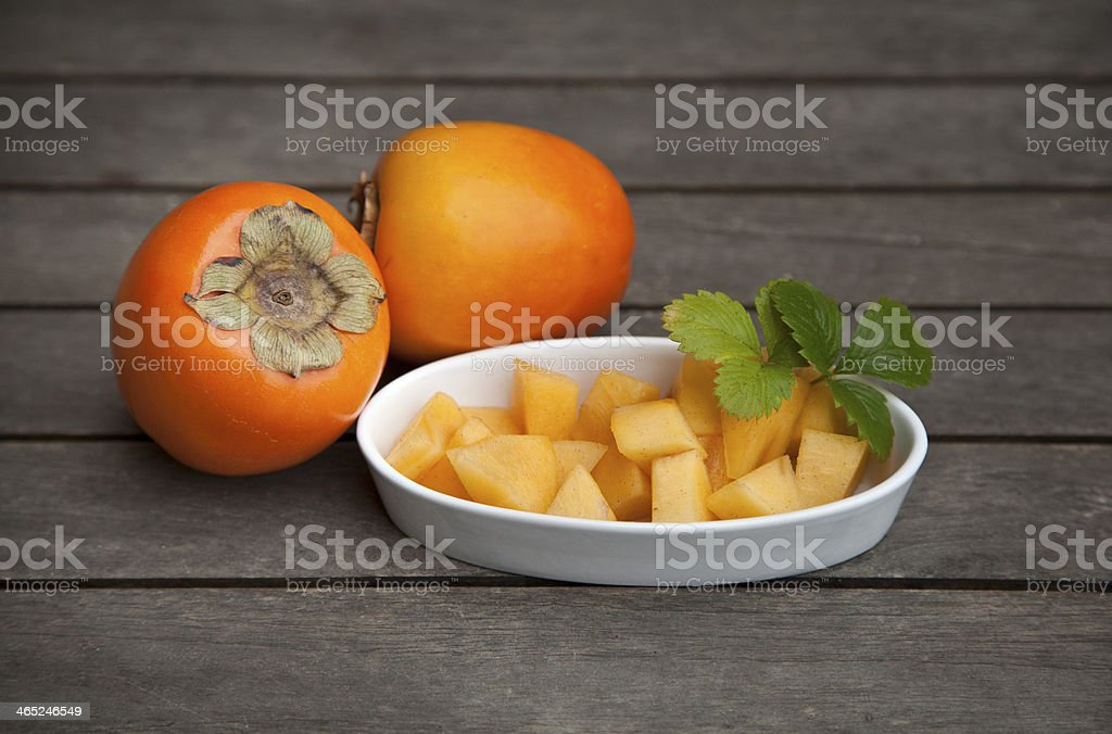 Wooden table with a dish of persimmon fruit chunks stock photo
