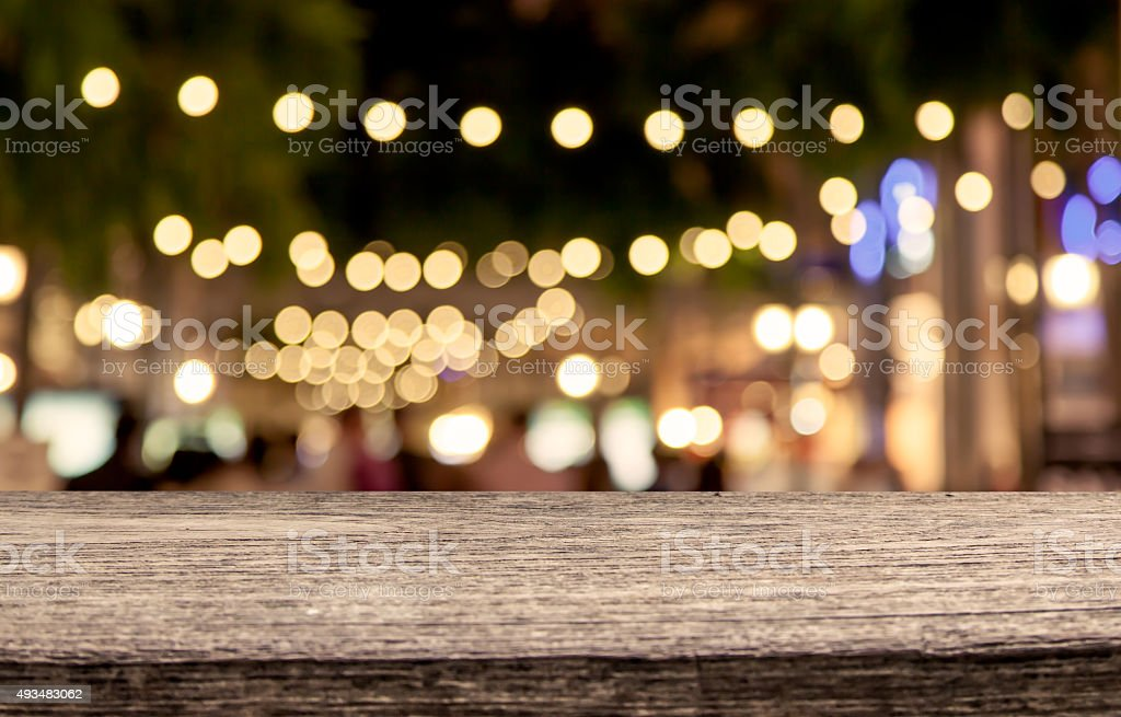 wooden table with abstract bokeh in night shopping mall stock photo
