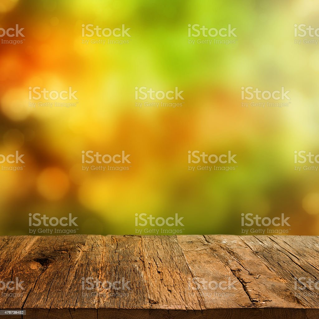 Wooden table with autumn background stock photo